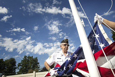 <p>Herold Markiewicz with the American Legion Honor Guard helps to raise a flag belonging to John O'Brien during the ribbon cutting ceremony at the new John O'Brien House Tuesday.</p>