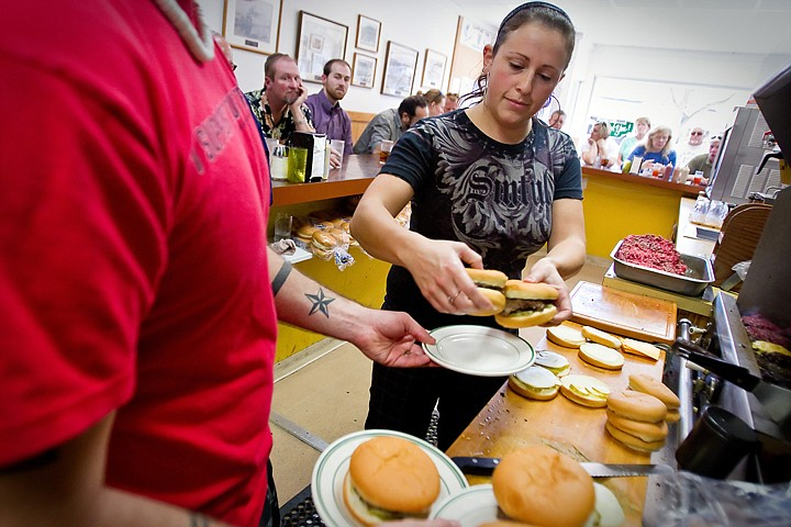 """<p>Tessa Weston plates a few orders after pulling the patties off the grill Friday during the lunch rush at Hudson's Hamburgers in downtown Coeur d'Alene. The popular 103-year-old restaurant was recently identified by USA Today as one of the """"51 Great Burger Joints"""" in the country.</p>"""