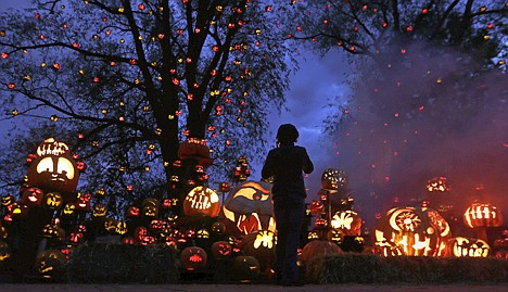 <p>While surrounded by hundreds of pumpkins, a girl stops to look at the illuminating jack o' lanterns at the Roger Williams Park Zoo in Providence, R.I., Monday. Some 5,000 carved pumpkins are on display for this year's Jack-o'-lantern Spectacular, one of the nation's largest jack-o'-lantern shows.</p>