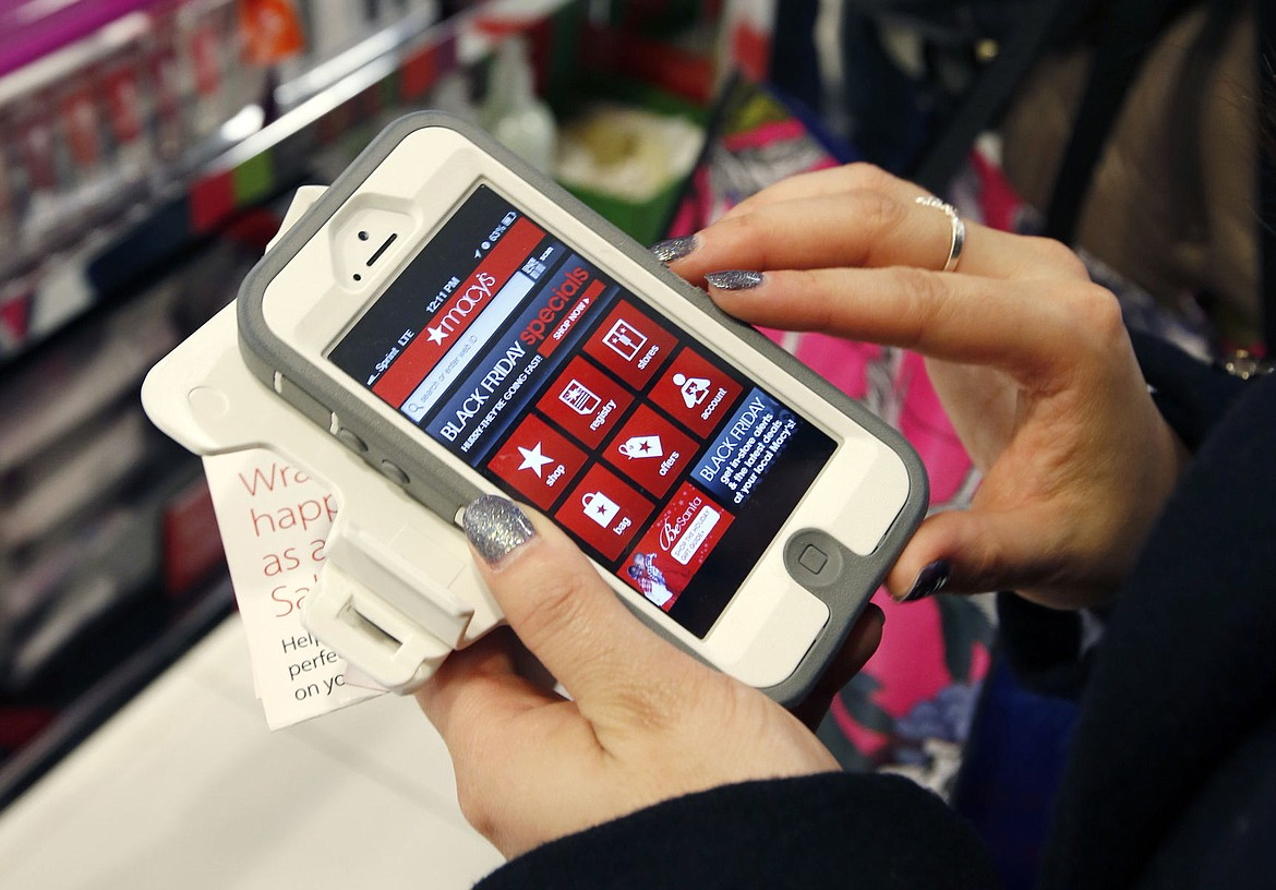 """<p>In this Friday, Nov. 23, 2012, file photo, Tashalee Rodriguez, of Boston, uses a smartphone app while shopping at Macy's in downtown Boston. Shoppers are flocking online Monday, Nov. 28, 2016, as """"Cyber Monday"""" sales hit their peak. Each year, during the busy holiday shopping weekend that kicks off on Thanksgiving and the Friday after, known as Black Friday, more and more shoppers decide to skip the mayhem in stores and shop online.</p>"""