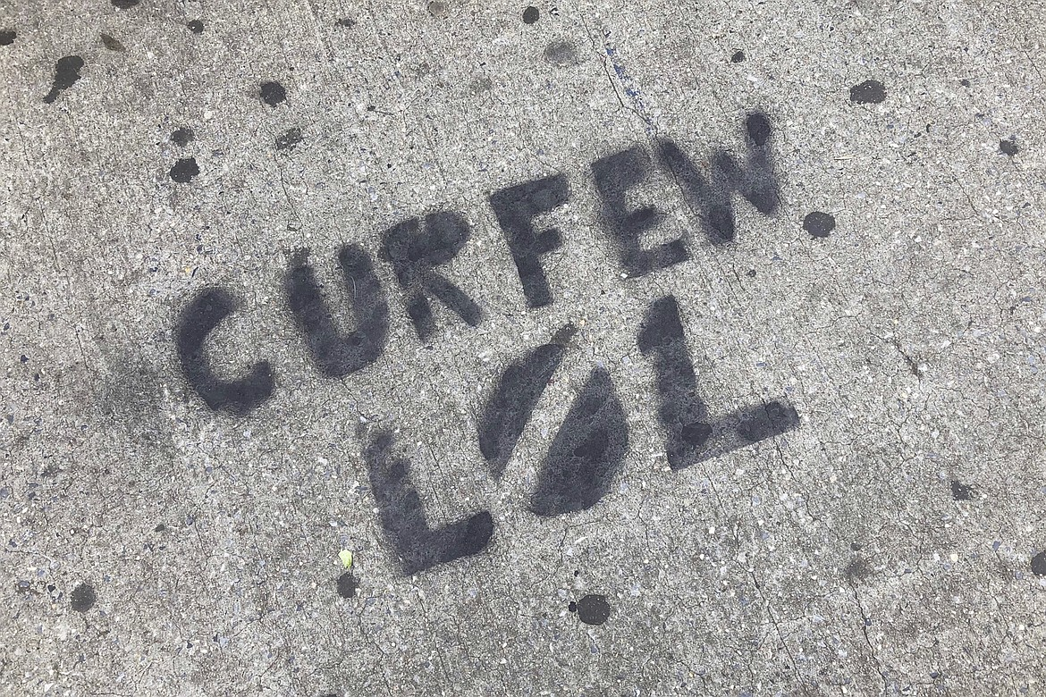 A sidewalk is spray painted with graffiti about New York City's curfew order, in the Brooklyn borough of New York, Tuesday, June 2, 2020. In New York City, nonviolent demonstrations against police brutality, sparked by the death of George Floyd at the hands of police in Minneapolis, were punctuated by people smashing storefront windows near Rockefeller Center and breaching the doors into the storied Macy's store, littering parts of Manhattan with broken glass.  (AP Photo/Mark Lennihan)