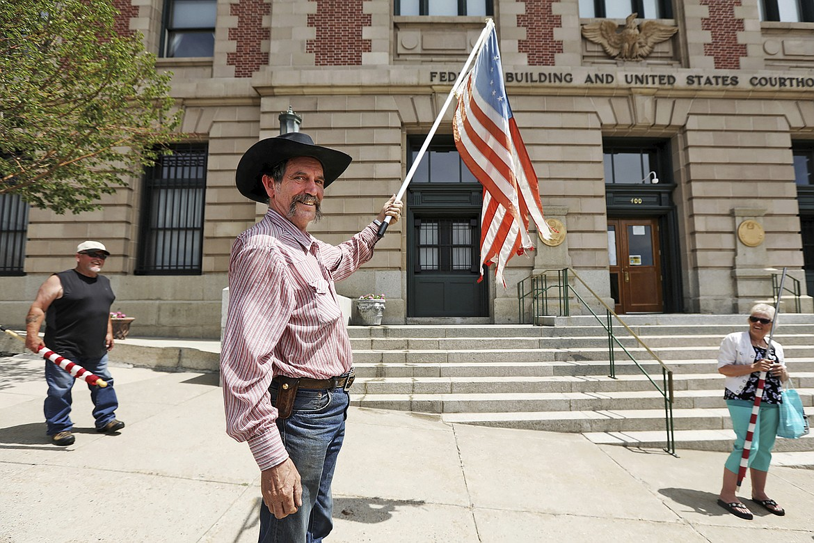 Bruce Leibold of Deer Lodge, Mont., waves a flag in front of the Mike Mansfield Federal Building and U.S. Courthouse in Butte, Mont., Wednesday, July 22, 2020. Kimberly and Rick Buck hold rolled flags, as they prepare to file a tort claim against Montana Gov. Steve Bullock's face mask order. The group's actions reflect discontent over state and local mask mandates. (Meagan Thompson/The Montana Standard via AP)