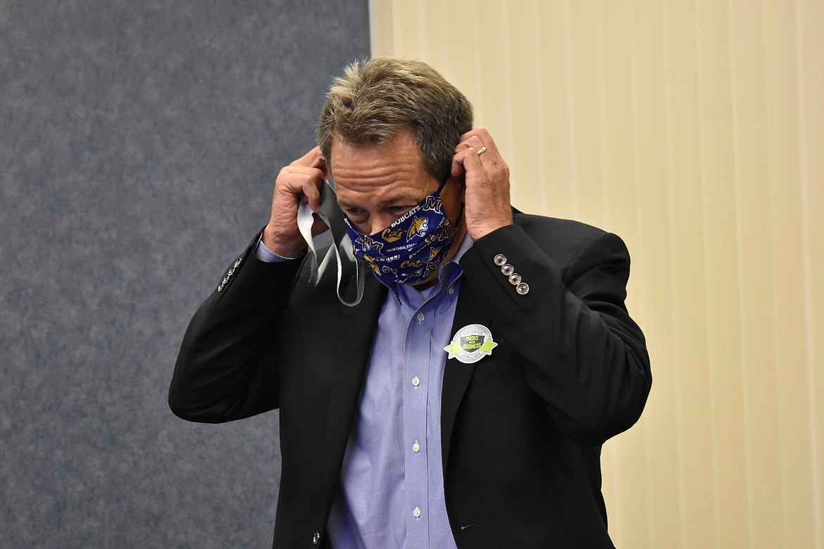 Montana Gov. Steve Bullock puts on a mask following a meeting with an economic recovery group in Billings, Montana on Thursday, July 23, 2020. Opponents of masks have been pushing back against public health mandates to wear them to help prevent the spread of the coronavirus. (AP Photo/Matthew Brown)