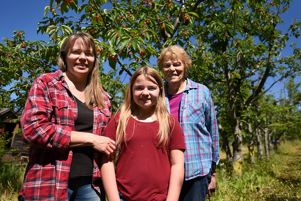 Denise Bowman Wermer, her daughter Ayla and her mother Marilyn Bowman stroll through the cherry trees as Bowman Orchards celebrates its 100th year in 2020. (Jeremy Weber/Daily Inter Lake)