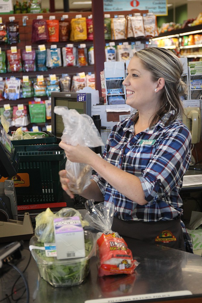 Brittany Blettner of Pilgrim's Market in Coeur d'Alene bags groceries for her favorite customers. Pilgrim's Market is a small grocer taking advantage of big data through a Point Of Sale software vendor.