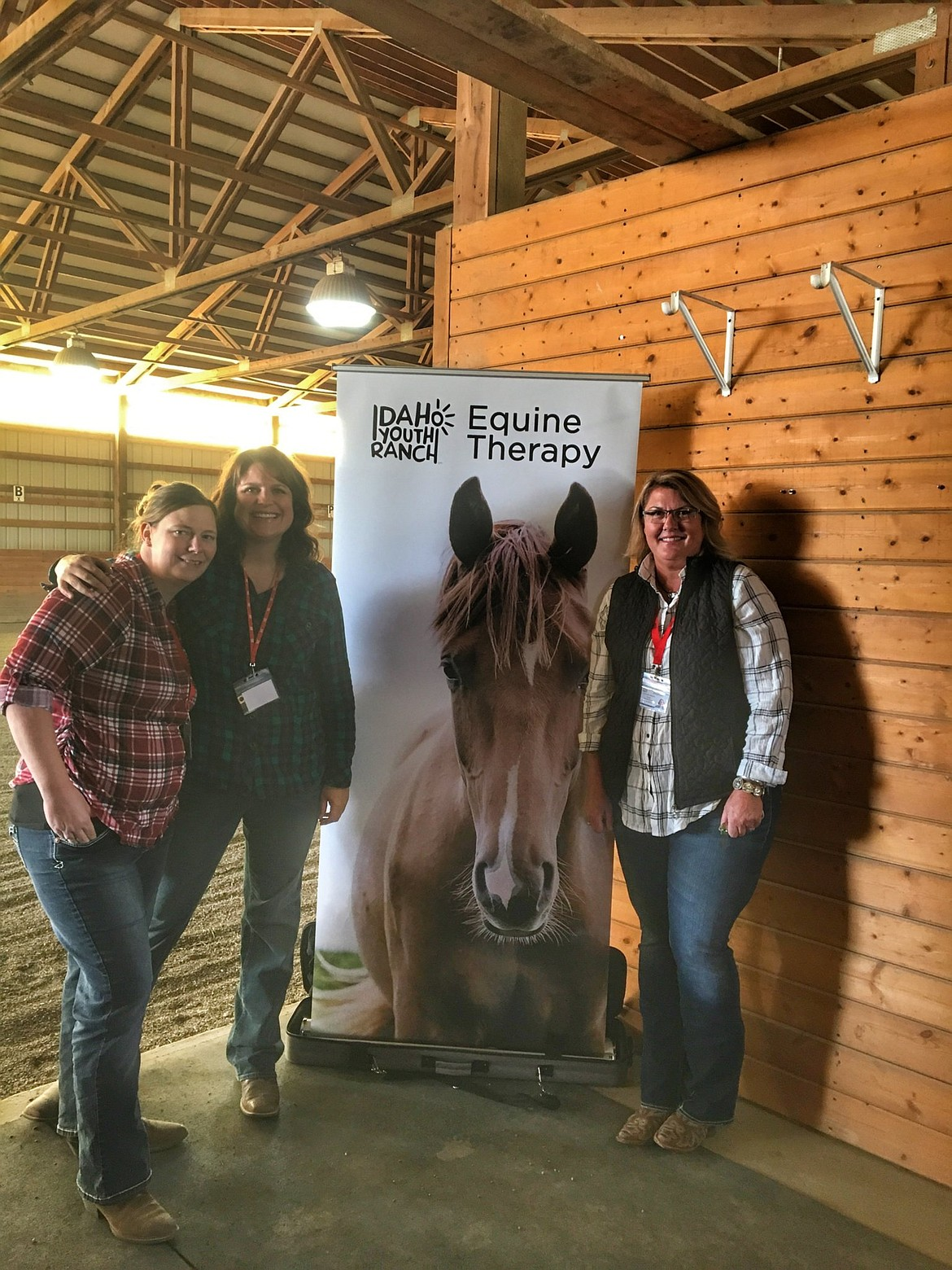 Samantha Roberts(L), equine therapist; Amanda Smith, program manager and therapist; and Christie Hartin(R), equine specialist, pose in front of the equine therapy program sign.