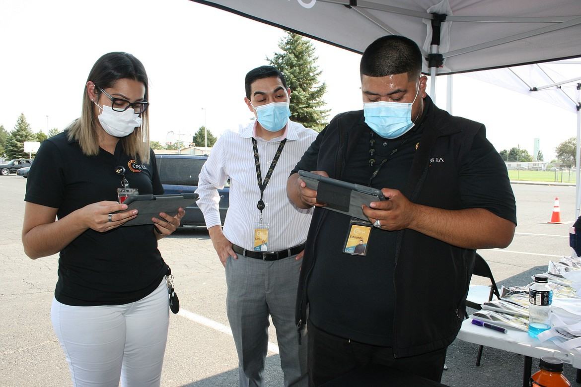 Rosa Martin, left, and Eduardo Saldivar, right, were volunteering at the drive-through census event in Mattawa when they realized they hadn't filled out census forms. Carlos Ruiz of the Mattawa CBHA clinic watches their progress.