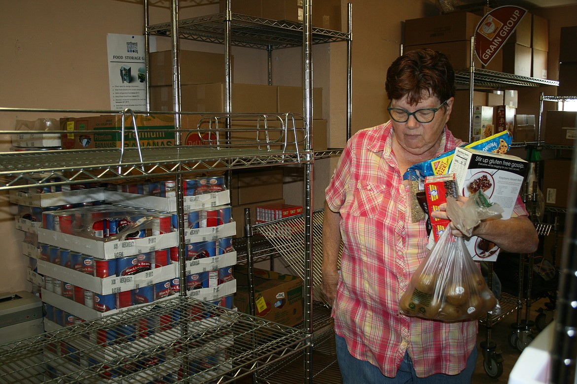 Othello Food Bank director Sharon Mobley collects items for a food box. The food bank will start a seniors-only day next week.