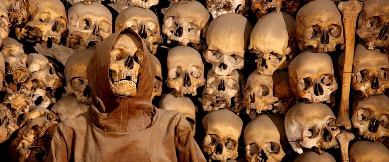Skulls, bones and a mummy in a Roman catacomb.