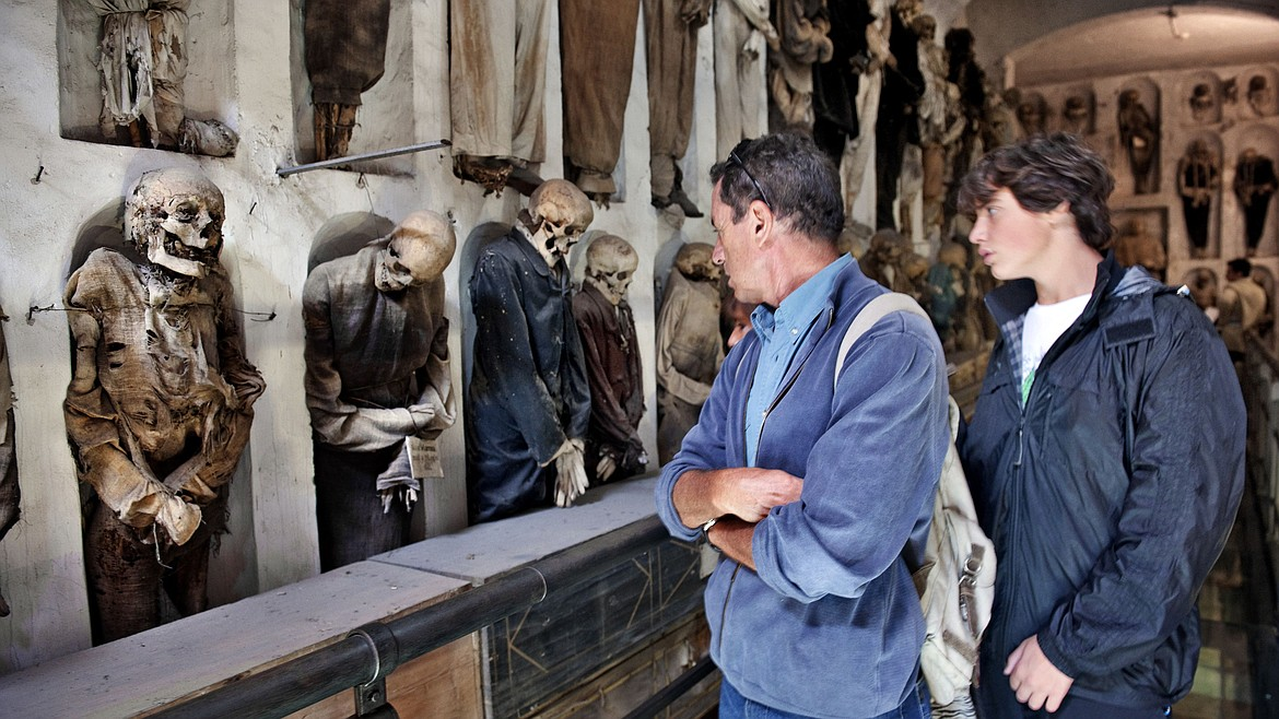 Visitors viewing mummies in the catacombs of Rome.