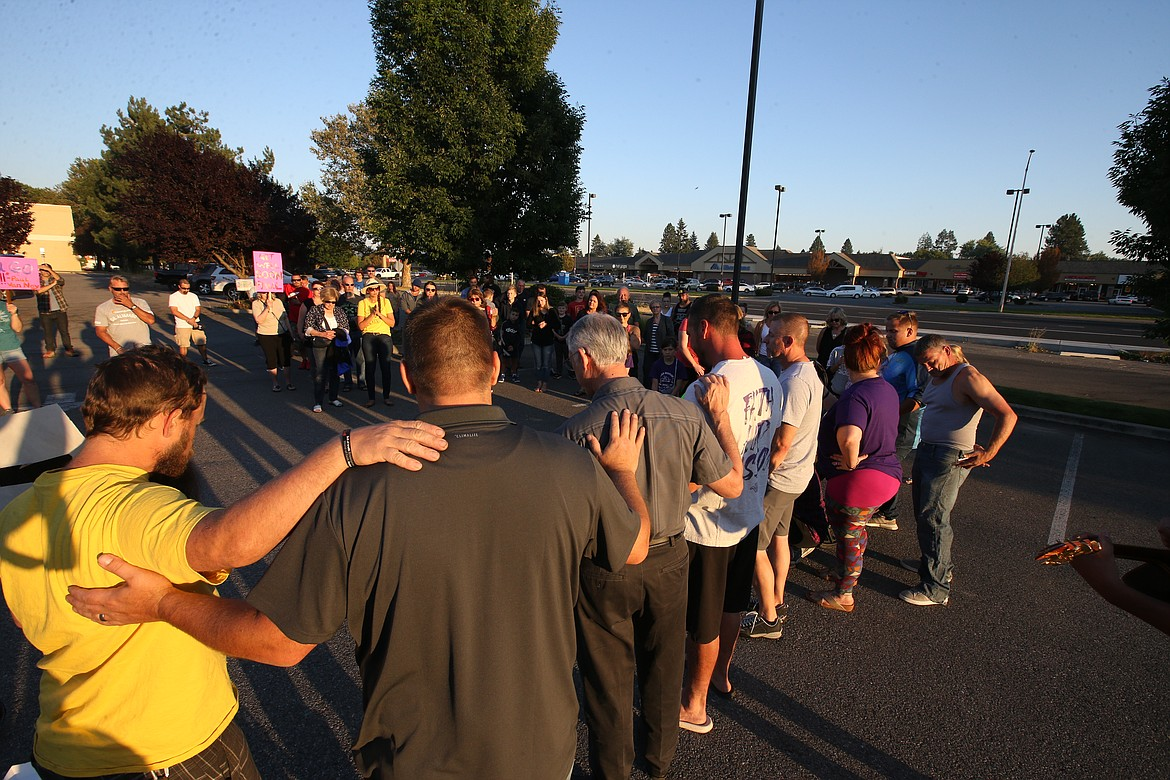 People pray for Pastor Paul Van Noy in a parking lot across the street from Kootenai Health on Wednesday.