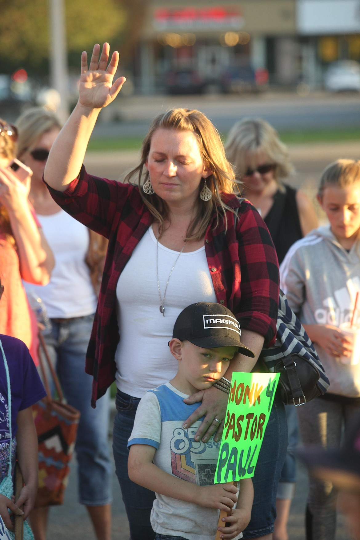 Kari Schueler and son Atticus participate in a prayer vigil for Pastor Paul Van Noy outside Kootenai Health Wednesday night.
