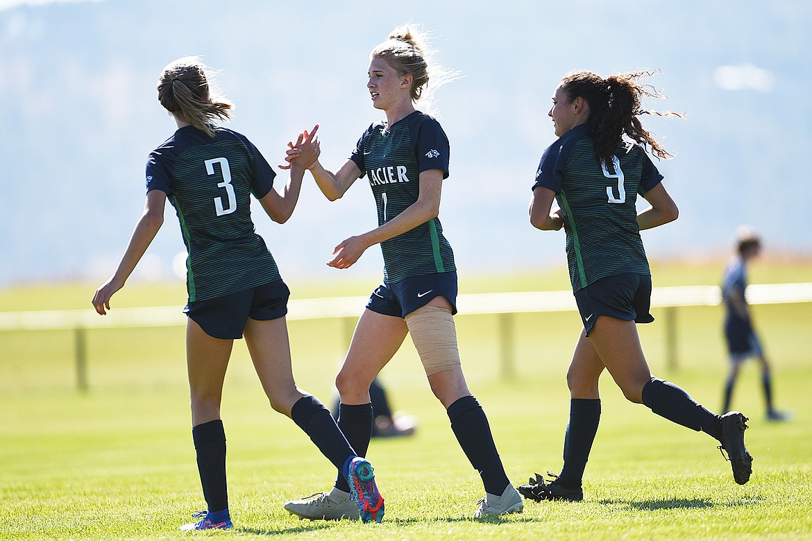 Glacier's Reagan Brisendine (3), Reese Leichtfuss (7) and Ady Powell (9) celebrate after Leichtfuss' goal in the first half against Missoula Big Sky at Glacier High School on Thursday. (Casey Kreider/Daily Inter Lake)