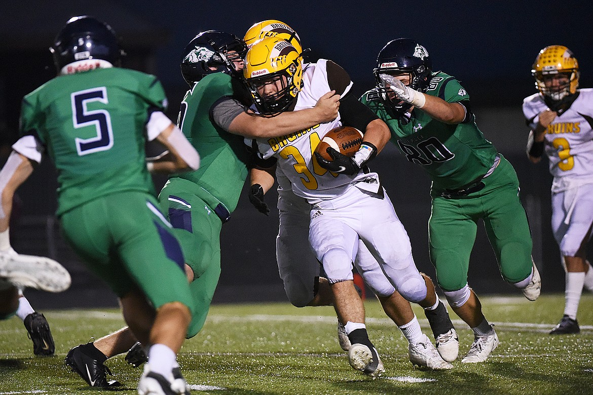 Glacier defensive linemen Rocco Beccari (56) and Ethan Diede (80) wrap up Helena Capital running back Tiegan Cozzle (34) on a third quarter run at Legends Stadium on Friday. (Casey Kreider/Daily Inter Lake)
