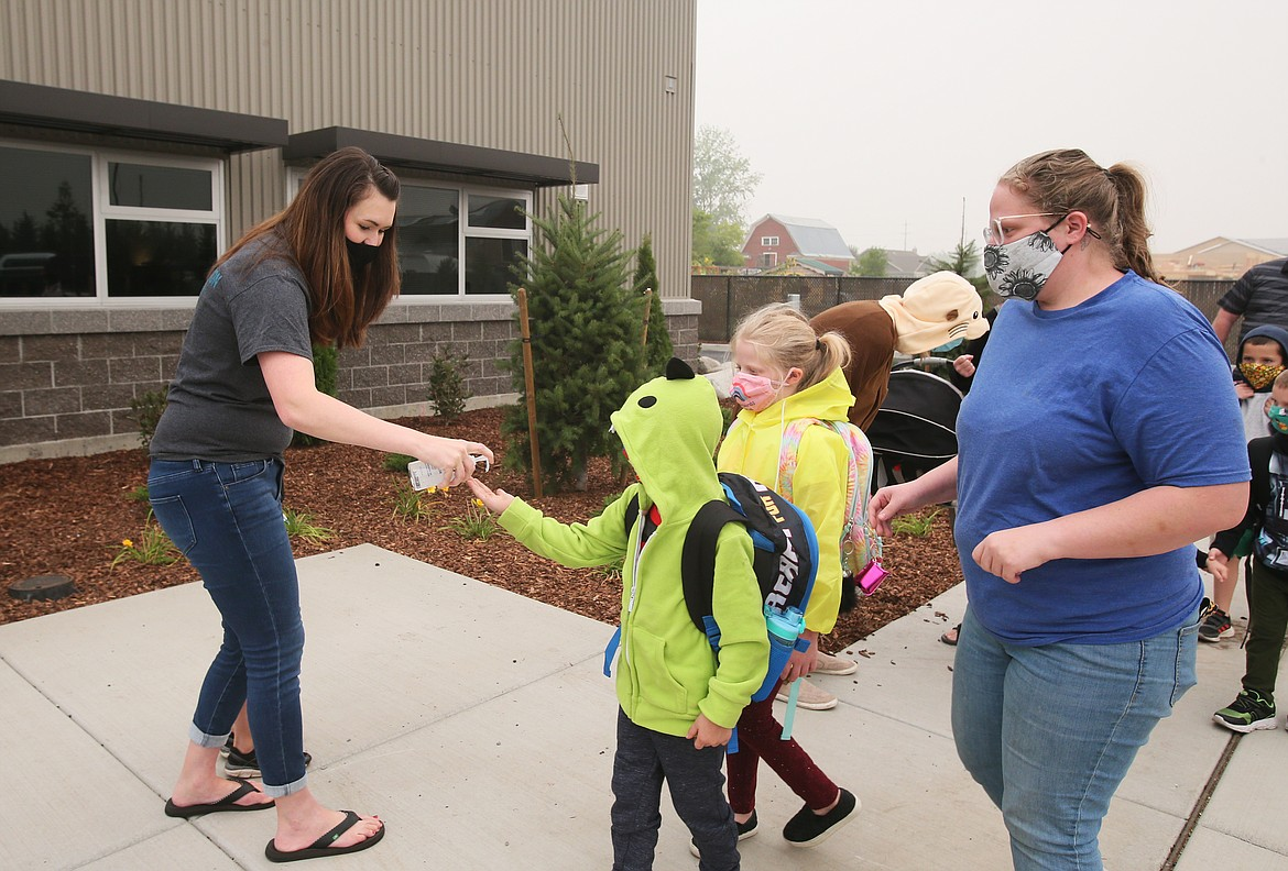 Elise Smith, PTA treasurer for Northwest Expedition Academy, gives everyone a squirt of hand sanitizer as they wait in line to enter the building on the first day of school.