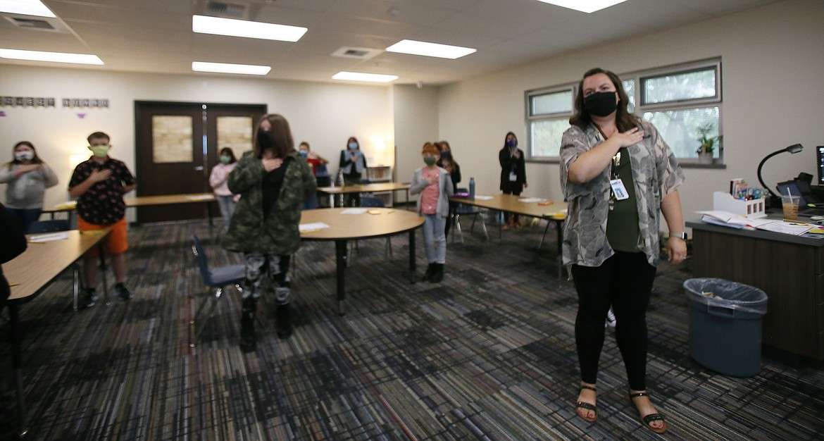 Fourth grade teacher Jessica Johnson, right, leads her class in the Pledge of Allegiance on the first day of school Monday at the new Northwest Expedition Academy on Prairie Avenue.