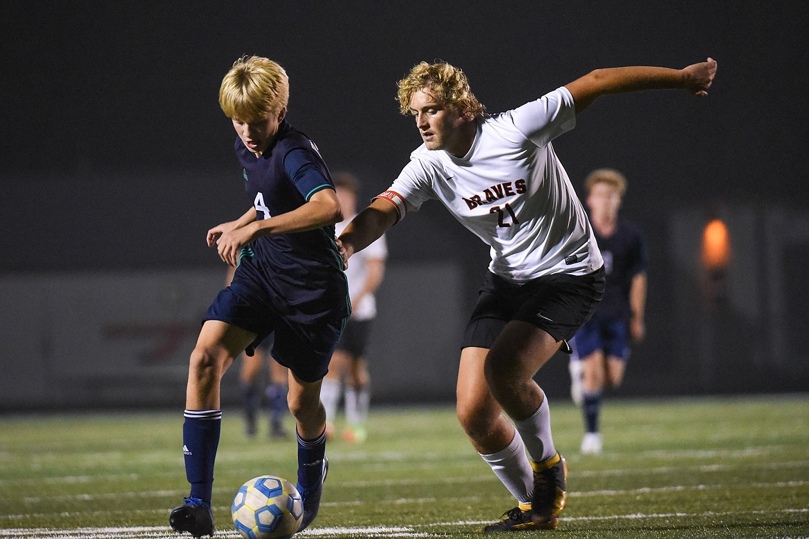 Glacier's Sam Ells (4) moves the ball upfield against Flathead's Ethan Vandenbosch (21) during crosstown soccer at Legends Stadium on Tuesday. (Casey Kreider/Daily Inter Lake)