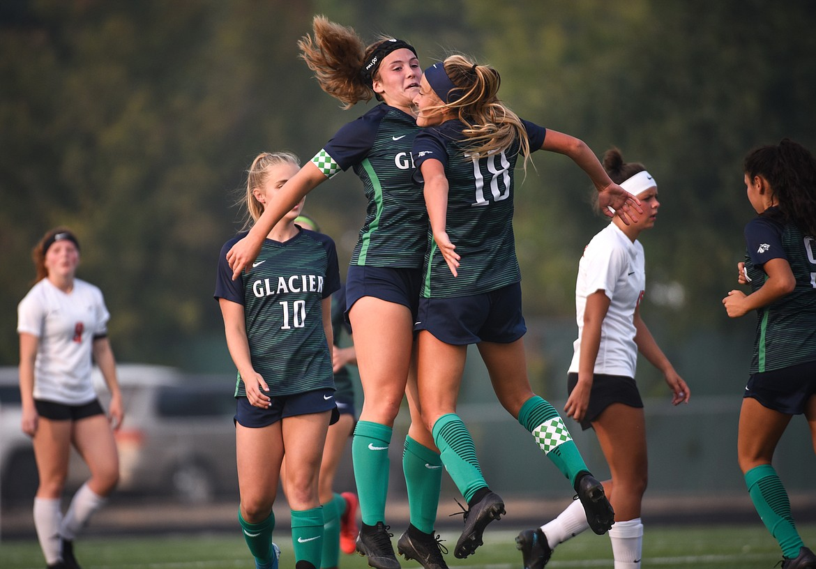 Glacier's Madison Becker (18) celebrates with Kenzie Williams (12) after Becker's first-half goal against Flathead during crosstown soccer at Legends Stadium on Tuesday. (Casey Kreider/Daily Inter Lake)