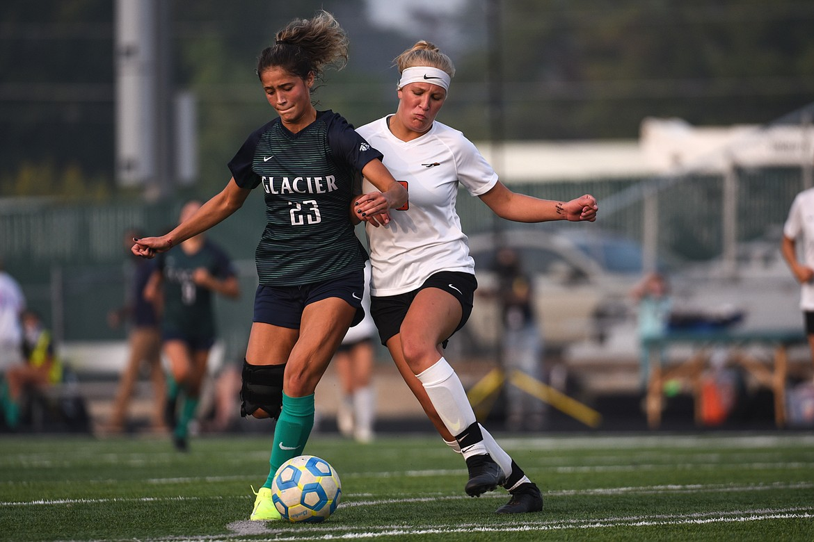 Glacier's Taylor Brisendine (23) and Flathead's Chloe Mohatt (8) battle for a loose ball during crosstown soccer at Legends Stadium on Tuesday. (Casey Kreider/Daily Inter Lake)