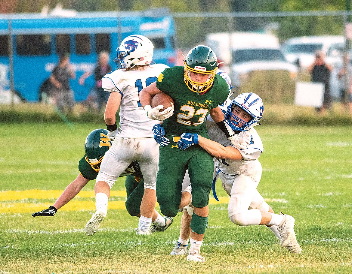 Ty Schwaiger tries to break a tackle against Columbia Falls' Zan McCallum. (Chris Peterson/Hungry Horse News)