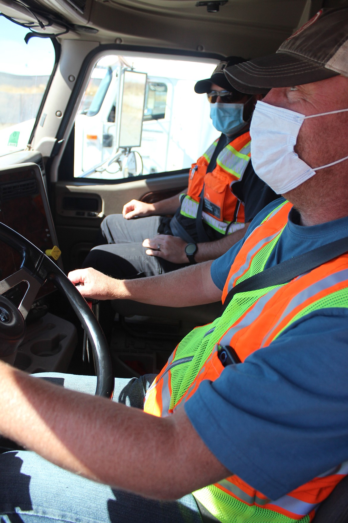 Bruce Nordstrom (foreground), of Coeur d'Alene, learns gear shifting in the cab from North Idaho College/Drive509 CDL Instructor Josh Munderloh. Wearing masks while inside the cab allows the course to be taught safely and in accordance with state guidelines.