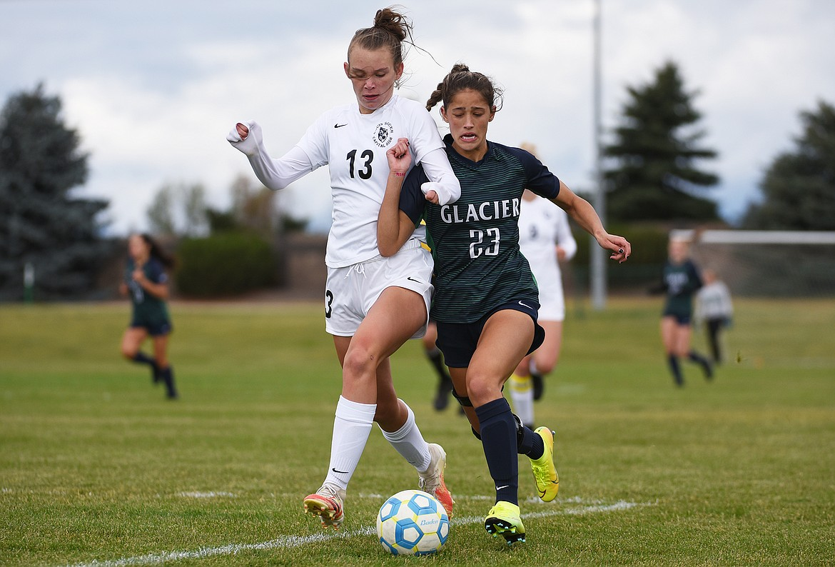 Glacier's Taylor Brisendine (23) battles for possession with Helena Capital's Rylee Cummings at Glacier High School on Saturday. (Casey Kreider/Daily Inter Lake)