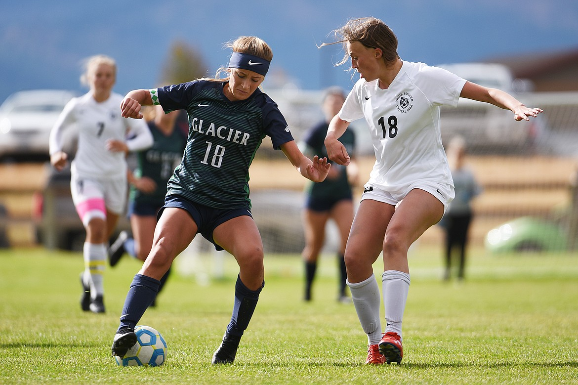 Glacier's Madison Becker (18) works the ball upfield against Helena Capital's Lauren Hoxie (18) at Glacier High School on Saturday. (Casey Kreider/Daily Inter Lake)
