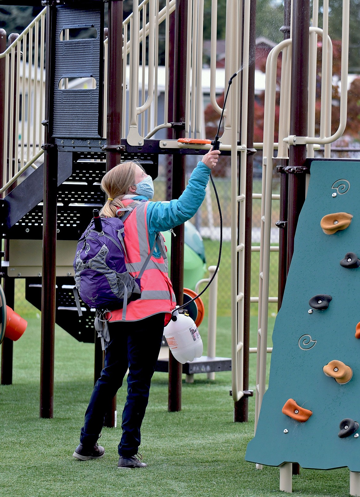 Playground supervisor Rebecca McQuary uses industrial sanitizer to clean the playground equipment between recess breaks at Muldown Elementary School. (Whitney England/Whitefish Pilot)
