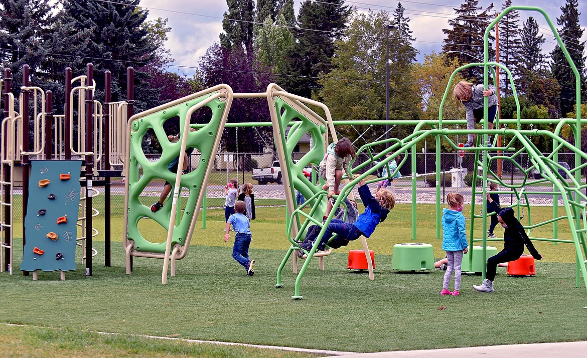 Muldown first graders play on the new playground outside of the elementary school. (Whitney England/Whitefish Pilot)