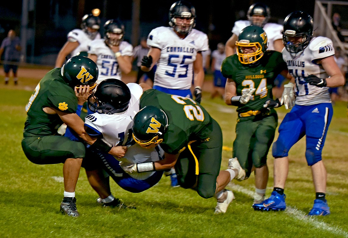 Whitefish's Ty Schwaiger sacks Corvallis quarterback Bryce Mayn with assist from his teammates during a game Friday night at home. (Whitney England/Whitefish Pilot)