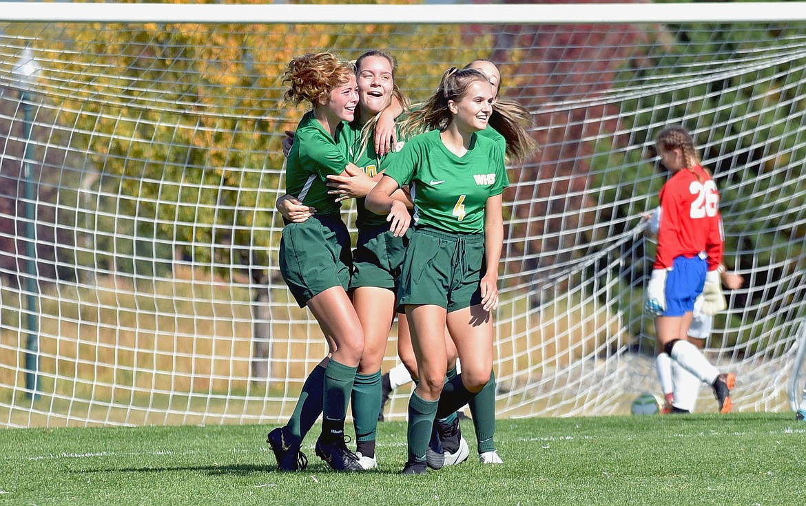 Whitefish players Brooke Roberts, Ali Hirsch and Sophie Olson celebrate a goal scored by Hirsch in the first half against Columbia Falls at Smith Fields on Saturday. (Whitney England/Whitefish Pilot)