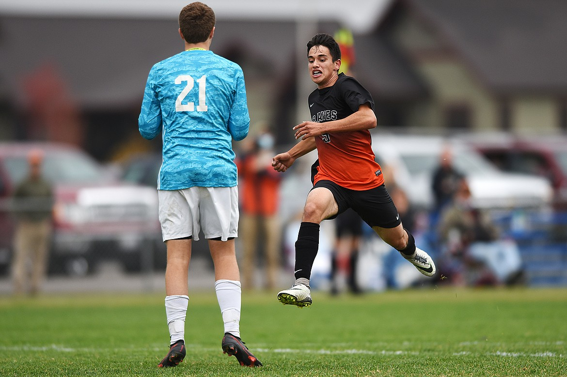 Flathead's Arsen Sokolov (9) makes a run at Butte goalkeeper Joe Schrader (21) as Schrader holds on to a save in the first half at Kidsports Complex on Saturday. (Casey Kreider/Daily Inter Lake)