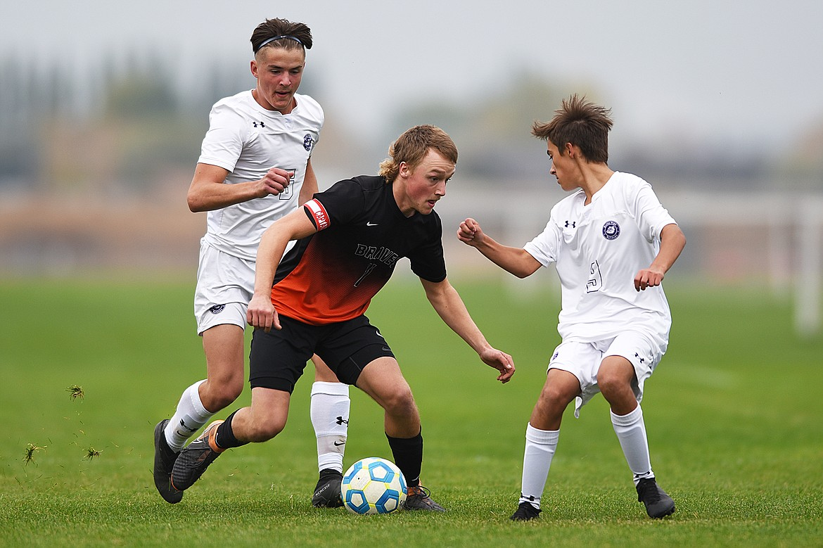 Flathead's Hudson Magone (1) pushes the ball upfield between Butte's Christian Sherman (6) and Riley Doyle (9) in the second half at Kidsports Complex on Saturday. (Casey Kreider/Daily Inter Lake)
