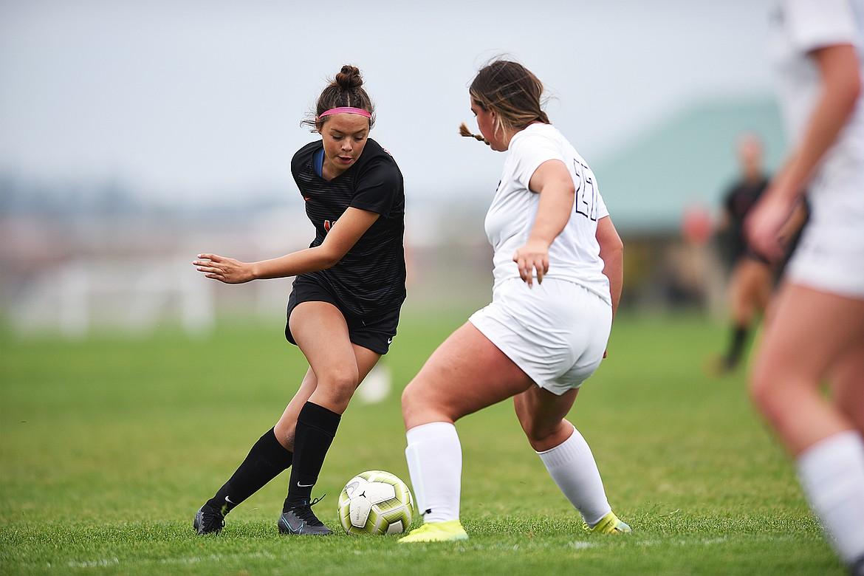 Flathead's Ashlynn Whiteman (10) looks to get around Butte's Emma Quist (27) in the first half at Kidsports Complex on Saturday. (Casey Kreider/Daily Inter Lake)