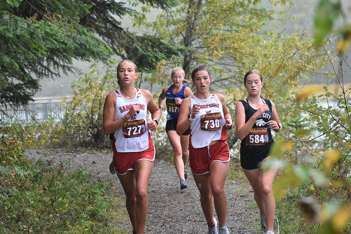 Sophomore Ara Clark (left) and junior Megan Oulman run side-by-side during Saturday's William Johnson Sandpoint Invitational.