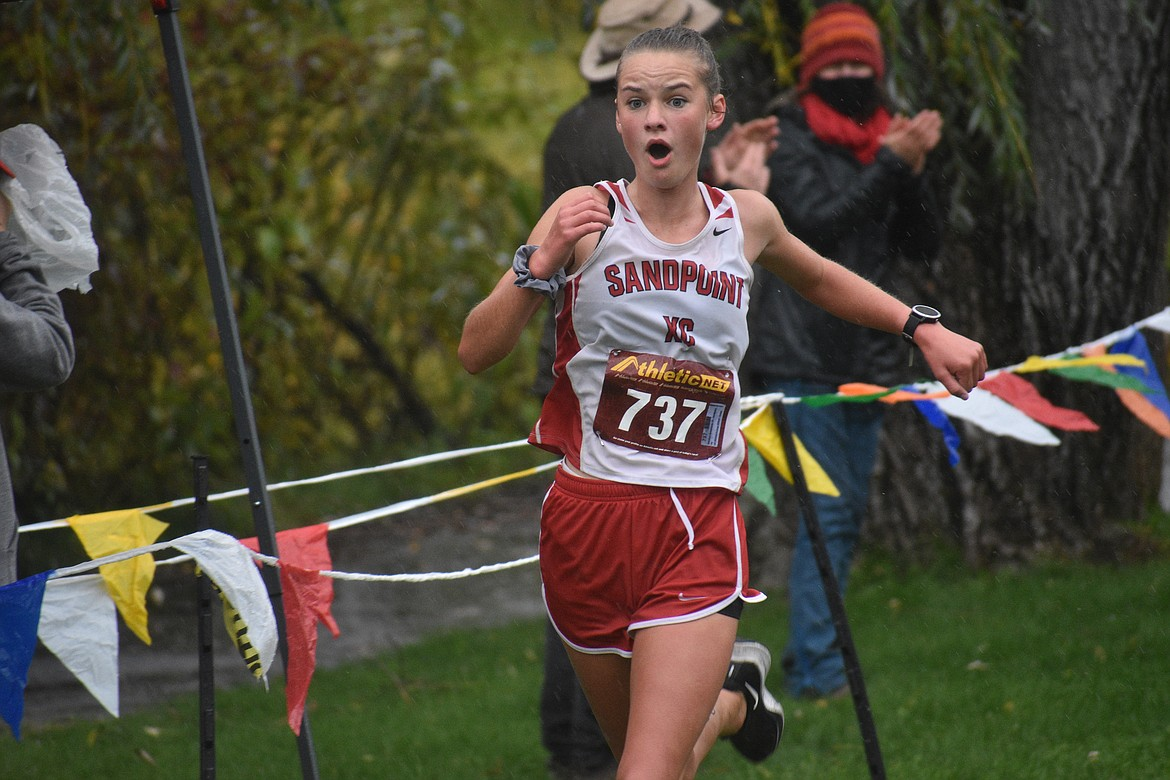 Tiffany Brown celebrates after crossing the finish line during Saturday's William Johnson Sandpoint Invitational.