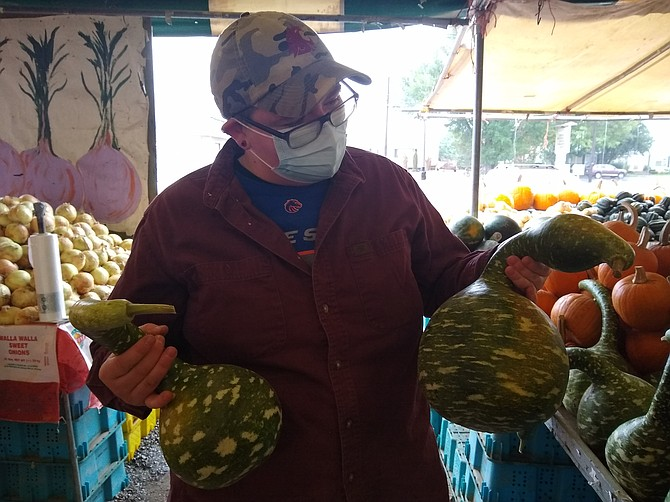 Liz Poteet shows off a pair of swan gourds, an heirloom gourd variety that many customers have never encountered before arriving at Poteet Produce.