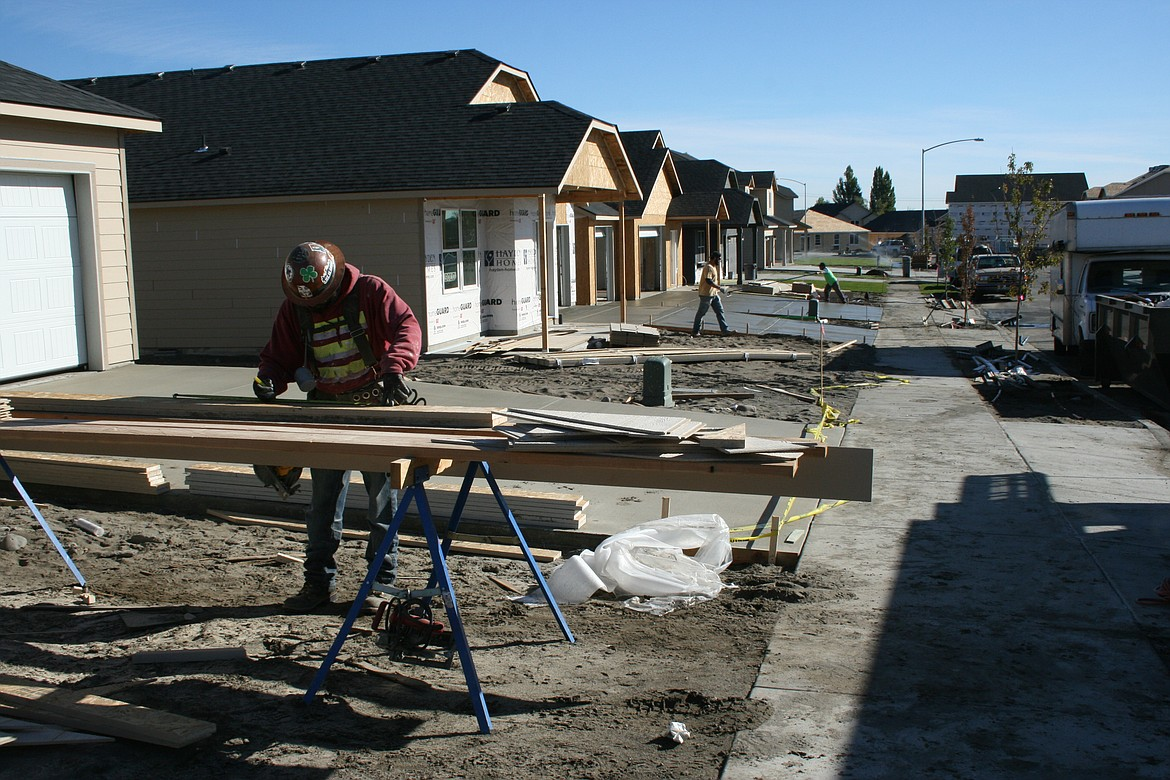 Construction workers swarm over a street of houses on a development near Moses Lake.
