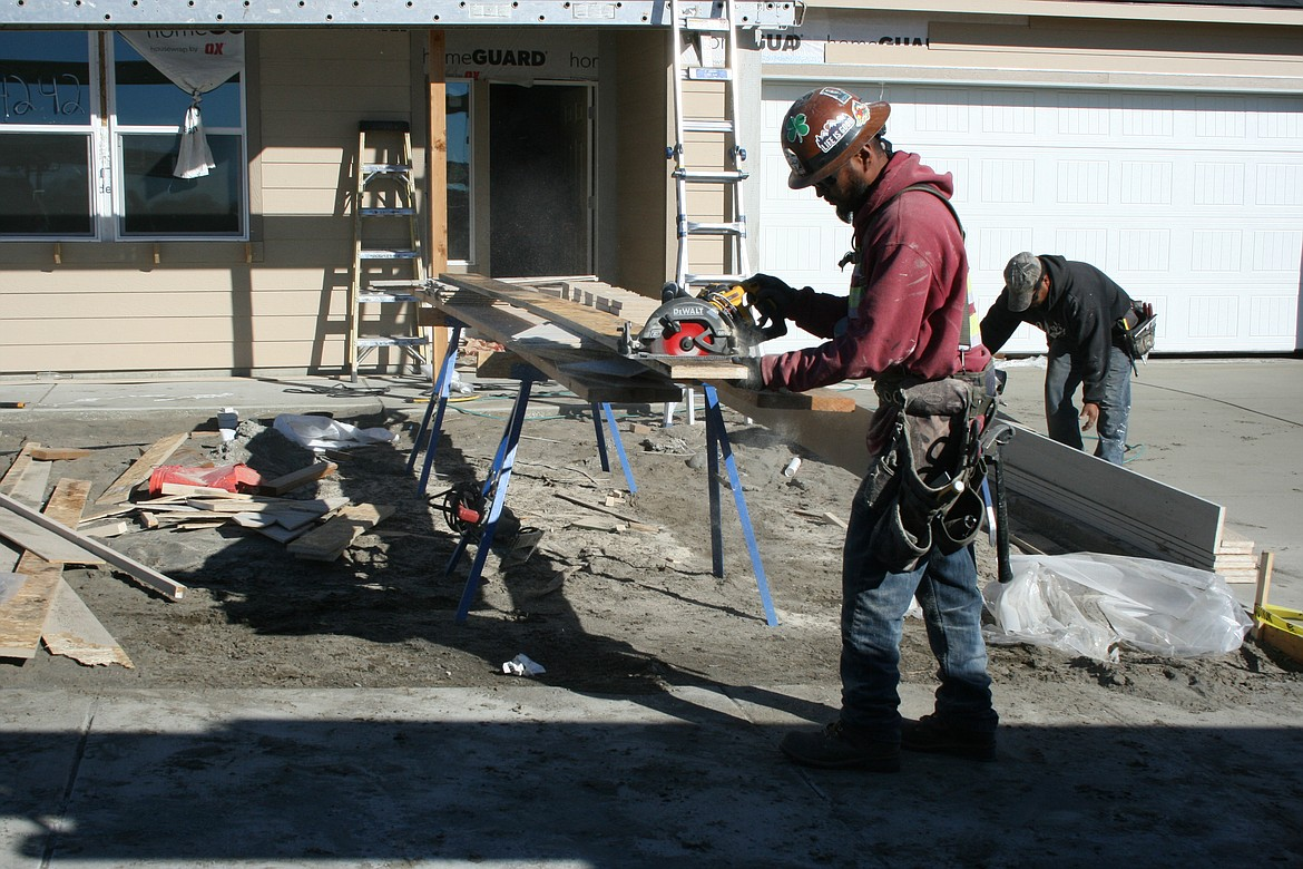Gustavo Silva prepares trim for a house under construction in a development near Moses Lake.