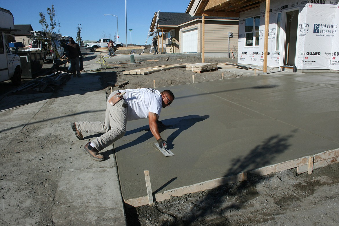 Javier Alvarado applies the finish coat to a driveway in a development near Moses Lake.