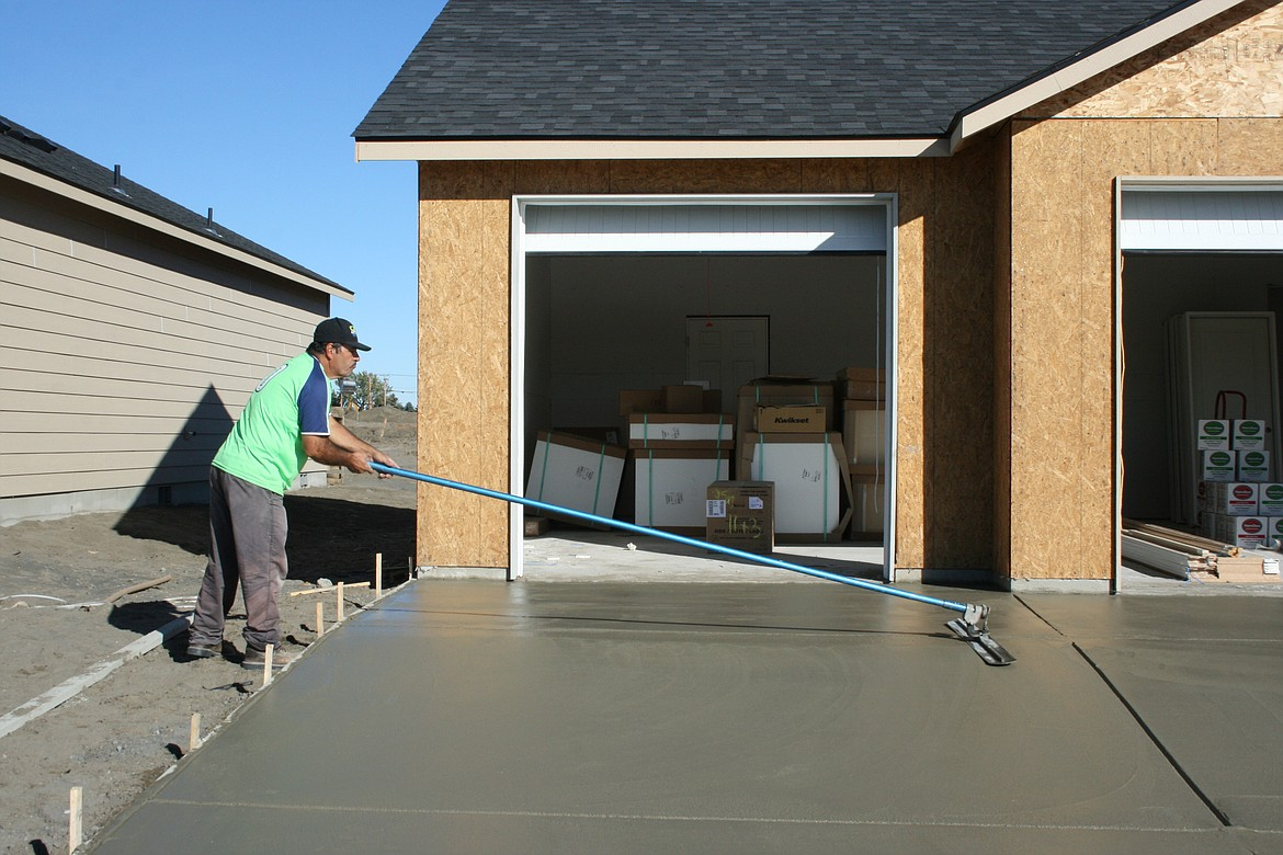 Leo Murado applies the finish to a driveway in a development near Moses Lake.