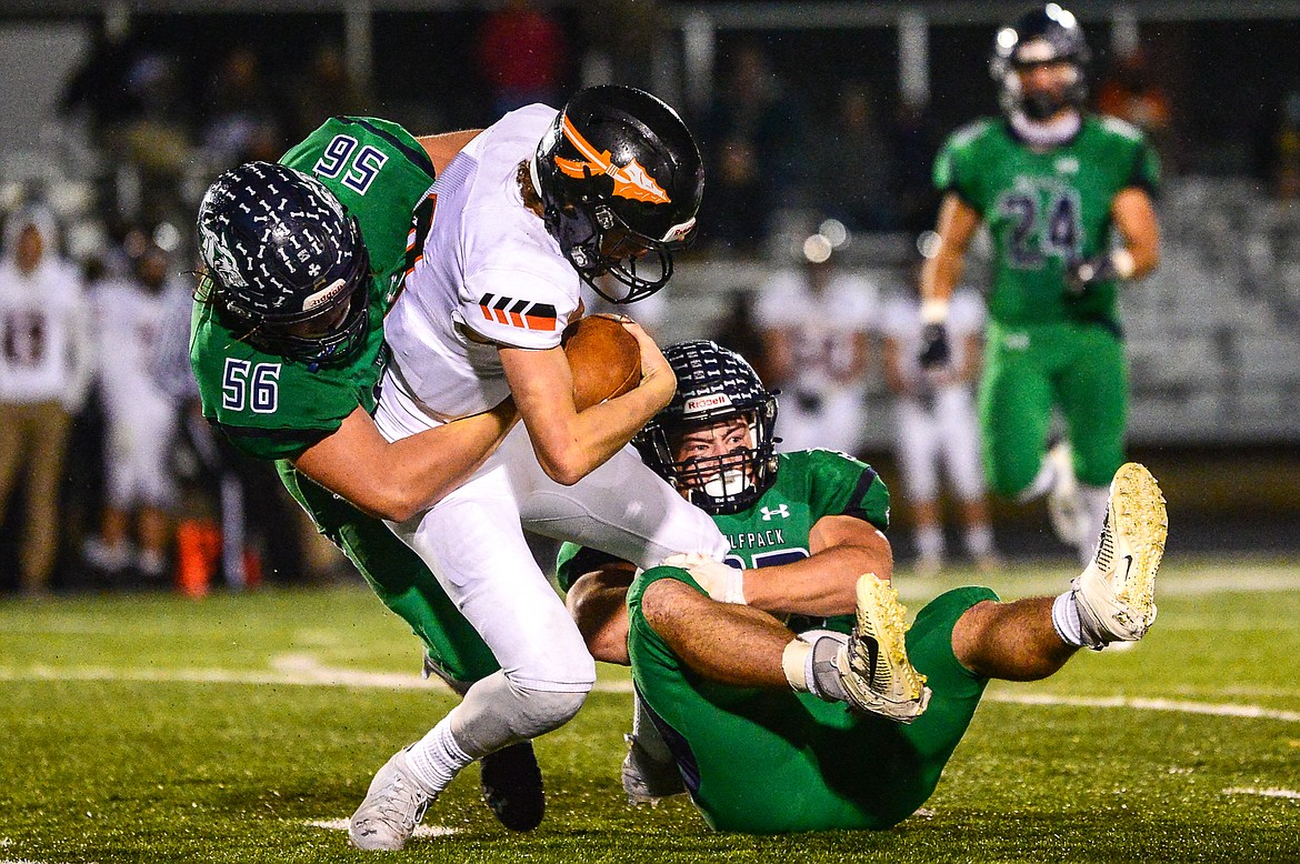 Glacier defenders Rocco Beccari (56) and Jake Rendina (33) sack Flathead quarterback Charlie Hinchey (9) in the third quarter in crosstown football at Legends Stadium on Friday. (Casey Kreider/Daily Inter Lake)