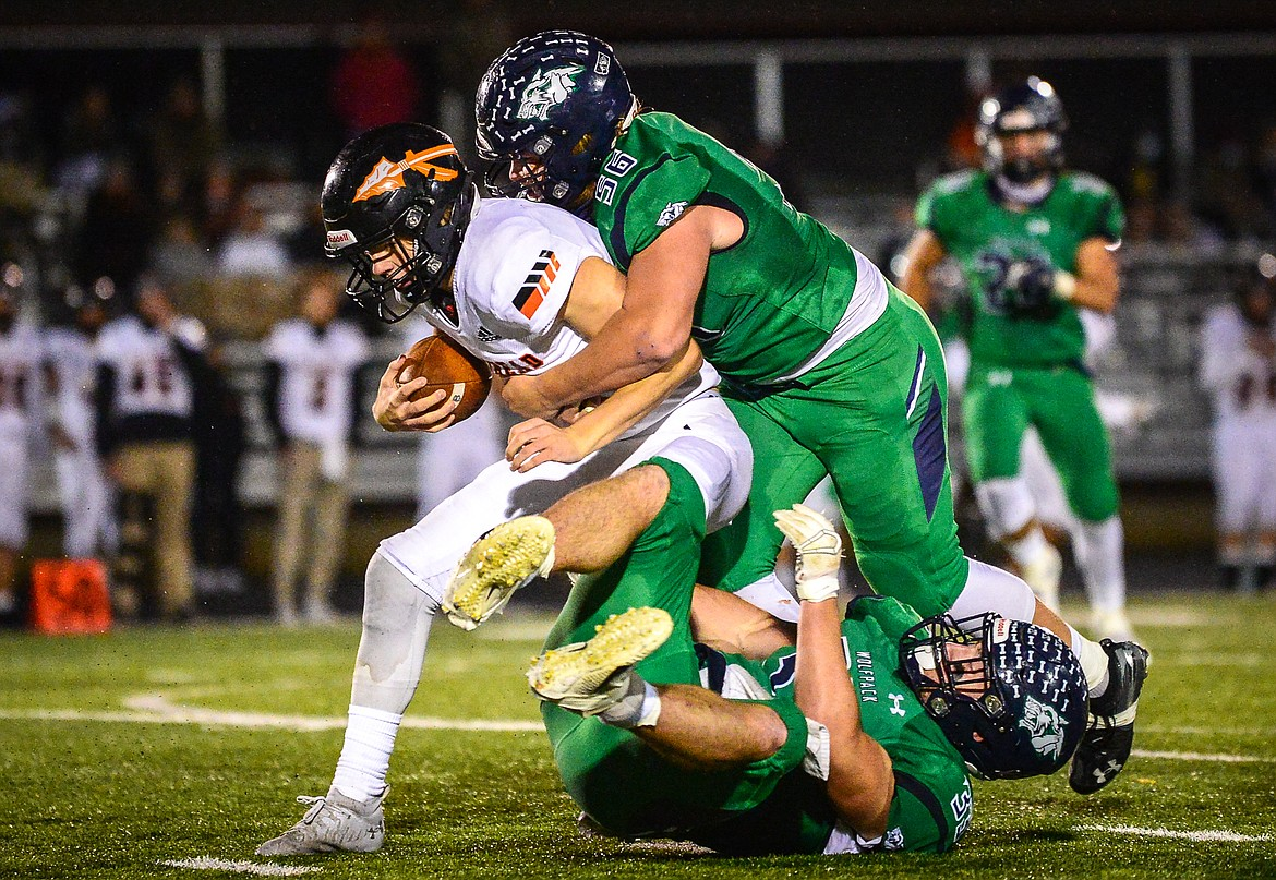 Glacier defenders Rocco Beccari (56) and Jake Rendina (33) sack Flathead quarterback Charlie Hinchey (9) in the third quarter in crosstown football at Legends Stadium on Friday. (Casey Kreider/Daily Inter
