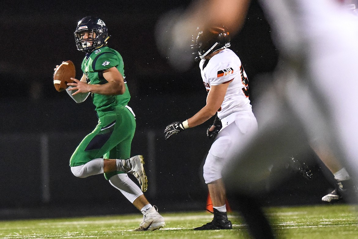 Glacier quarterback JT Allen (3) is chased out of the pocket by Flathead defensive lineman Elijah Owens (56) in the third quarter during crosstown football at Legends Stadium on Friday. (Casey Kreider/Daily Inter Lake)