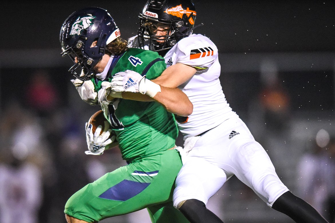 Glacier tight end Luke Bilau (4) is brought down by Flathead defensive back Nicolas Gustafson (8) in the second quarter during crosstown football at Legends Stadium on Friday. (Casey Kreider/Daily Inter Lake)