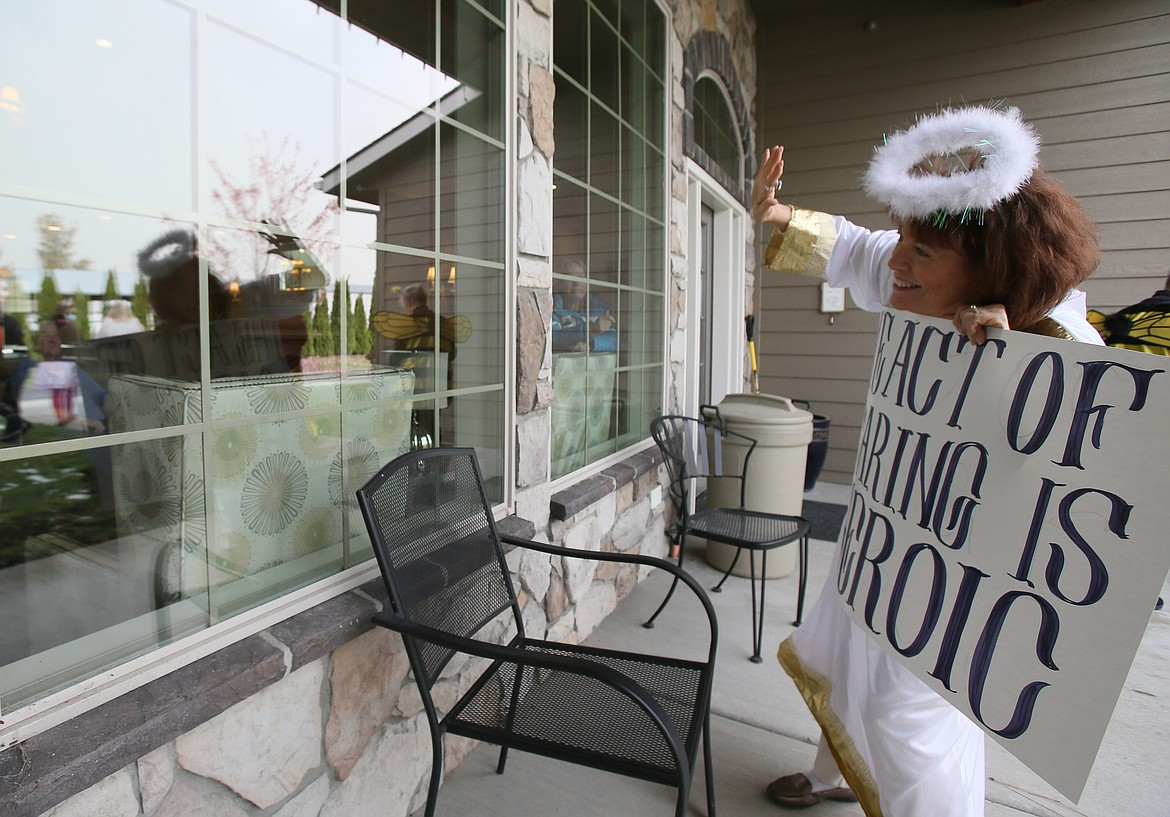 """Silver Angels for the Elderly volunteer Peggy Lemm waves through the window to Renaissance at Coeur d'Alene residents during a Halloween parade Friday. Her sign reads, """"The act of caring is heroic."""""""