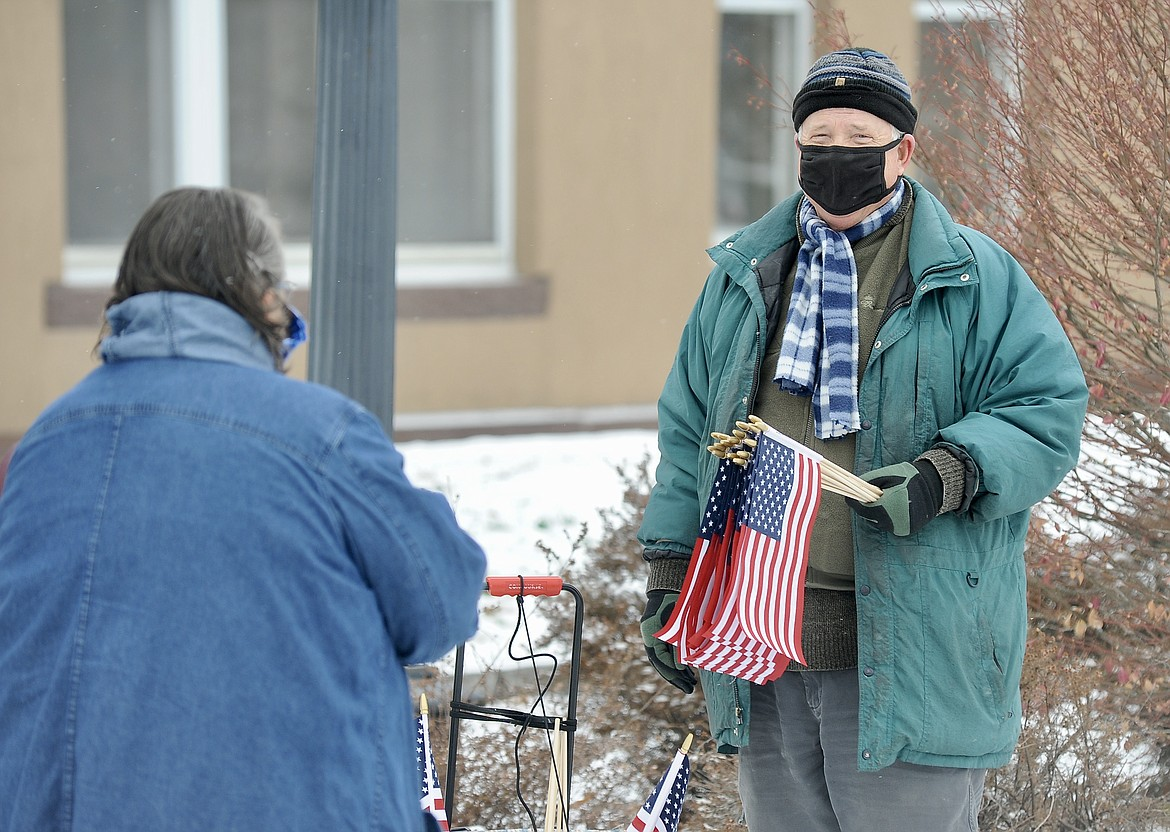 Al Wellenstein hands out flags at a Veterans Day ceremony Wednesday, Nov. 11, at Depot Park in Kalispell. (Matt Baldwin/Daily Inter Lake)