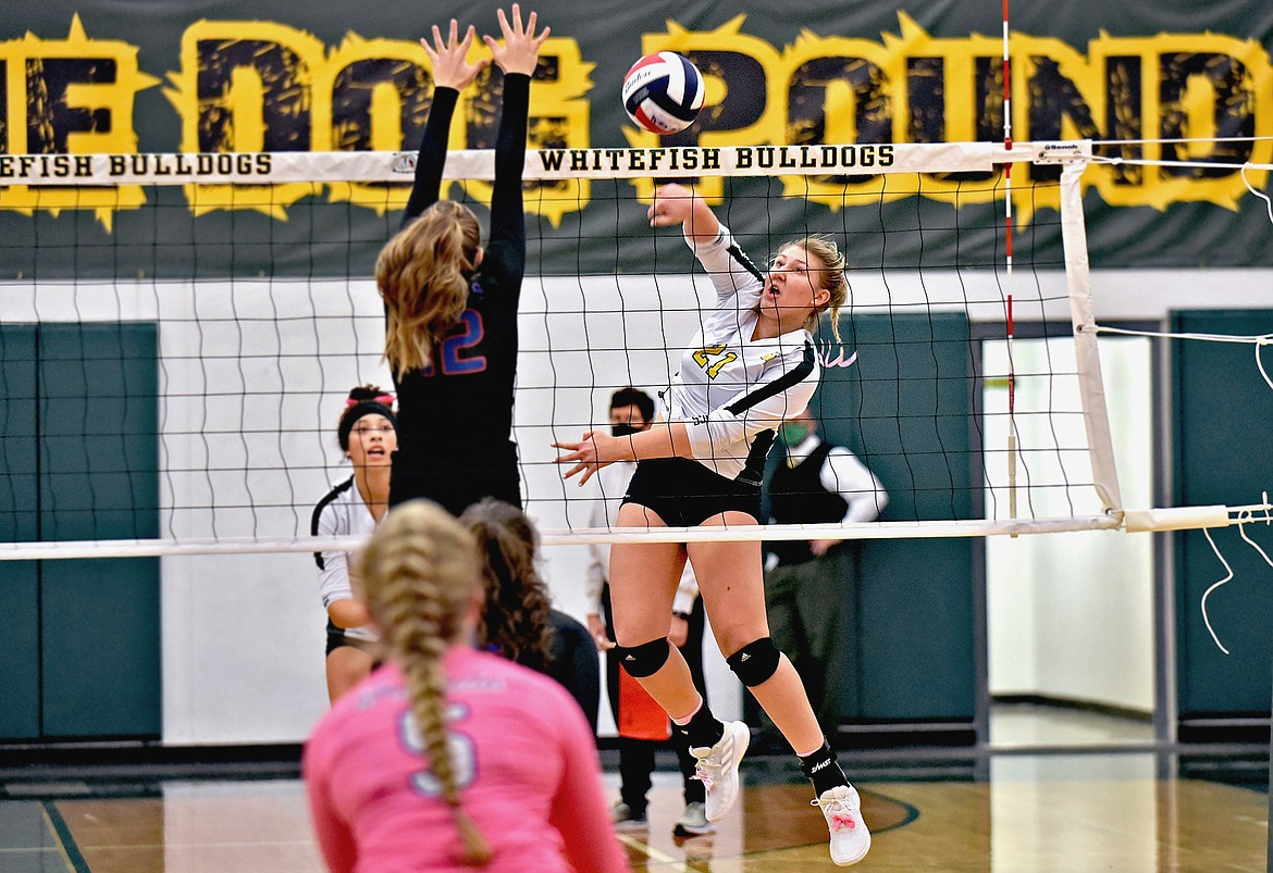 Lady Bulldog Brook Smith strikes the ball powerfully past a Columbia Falls blocker during a match earlier in the season. (Whitney England/Whitefish Pilot)