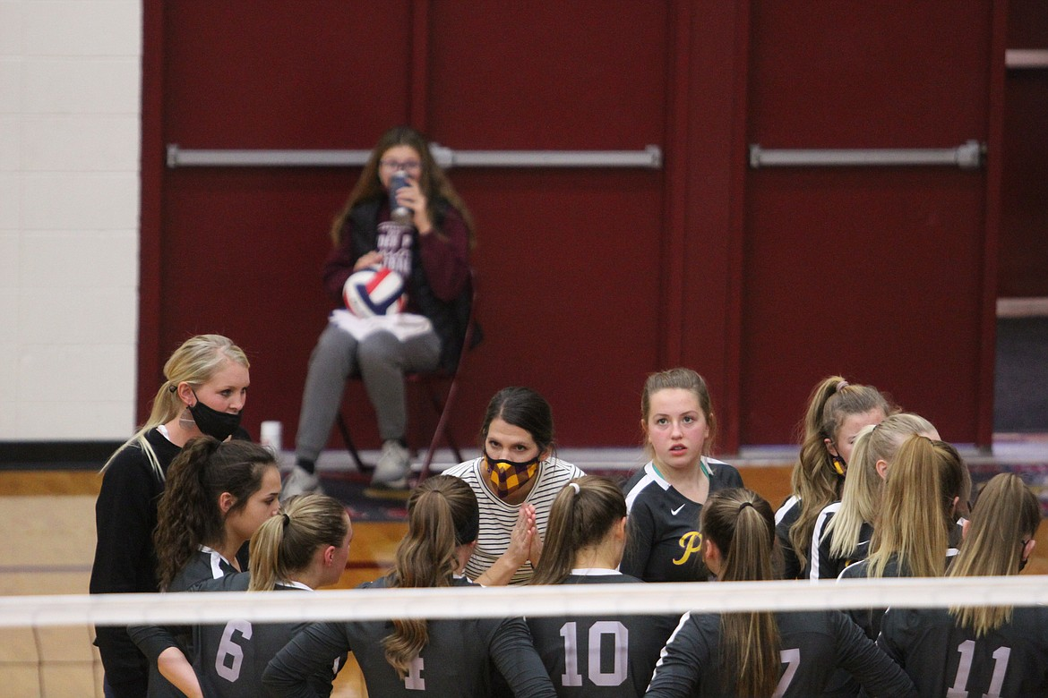 Polson head coach Lizzy Cox (center, yellow mask) addresses her team during the Lady Pirates' match with Ronan on Saturday in Sidney. (Dillan Schorfheide/Sidney Herald)