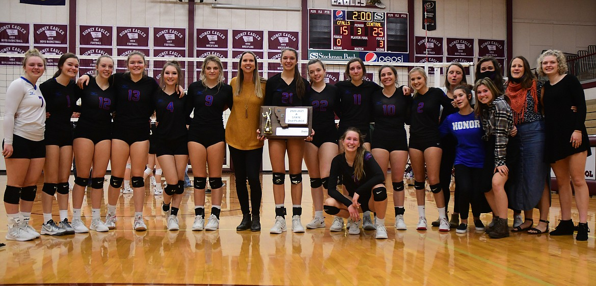 The Wildkat volleyball team poses with their second place State A trophy after the championship match in Sidney on Saturday. Back row, left to right: McKenna Rensel, Rhys Sharpton, Lauren Falkner, Grace Gedlaman, Isabel Brandeberry, Hannah Schweikert, head coach Jolandie Brooks, Mady Hoerner, Maddy Collins, Jazzy Marino, Madeline Stutsman, Haylee Lawrence, coach Anna Danley, coach Haley Belgarde, coach Gretchen Miller, Demye Rensel. Front row, left to right: Dillen Hoerner, Jayden Webb, Aspen Dawson.   (Teresa Byrd/Hungry Horse News)